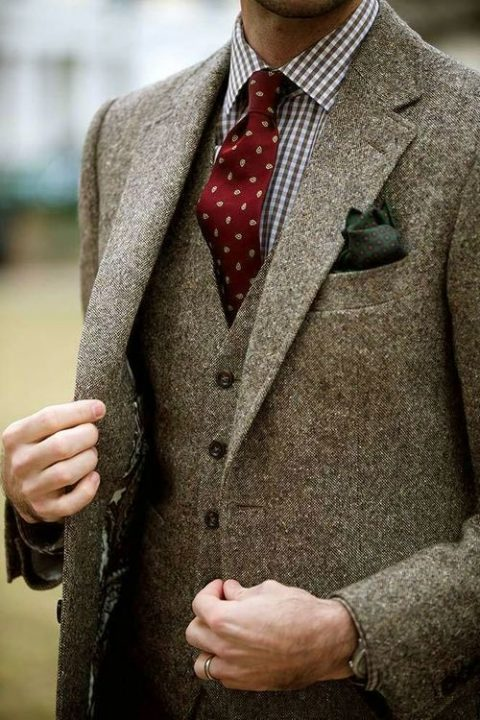 a tweed three piece wedding suit with a gingham shirt and a red printed tie