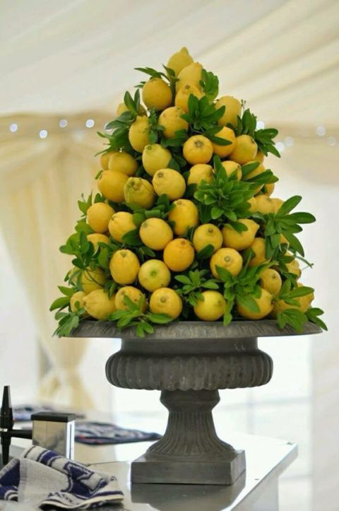 a vintage urn with lemons and greenery for a tropical wedding
