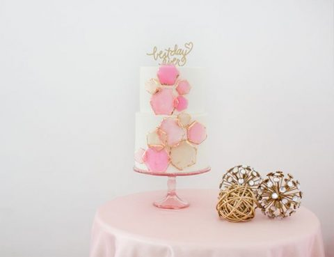 a wedding cake with blush and pink gilded edge hex decor