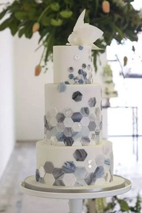 a wedding cake with marble hexagon decor and a sugar flower on top