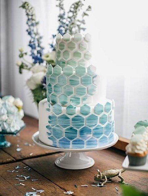 a wedding cake with ombre green to blue hex tiles