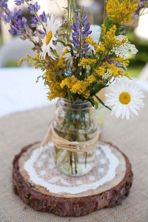 a wedding centerpiece with a wood slice, a doily and wildflowers