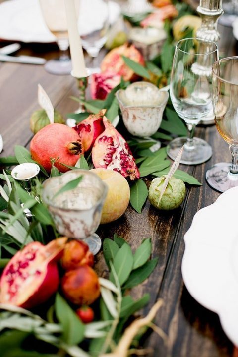a wedding table runner of greenery, pomegranates and apples and with candle holders