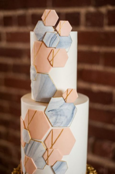 a white cake decorated with orange and marble hexagons