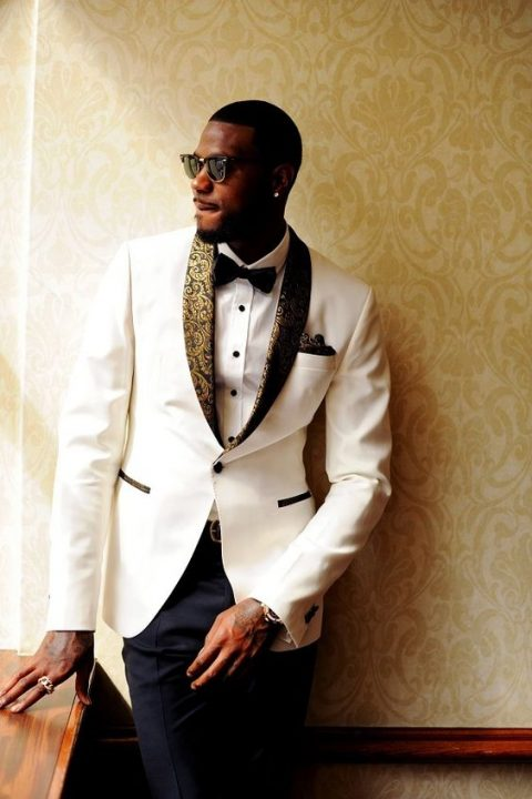 a white dinner jacket with gold and black patterned lapels and dark grey trousers