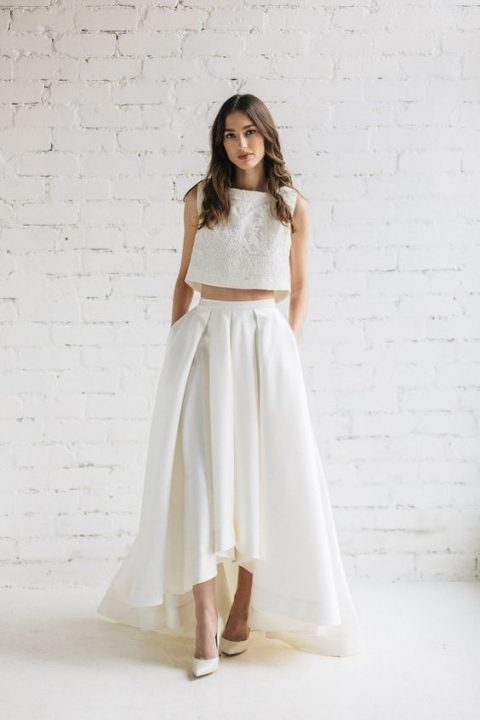 a white lace crop top and a plain high low pleated skirt