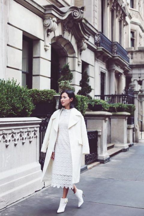 a white lace midi dress, white ankle booties and a white coat