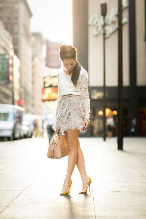 a white long sleeve top, a neutral feather mini skirt, a brown belt and neon yellow shoes