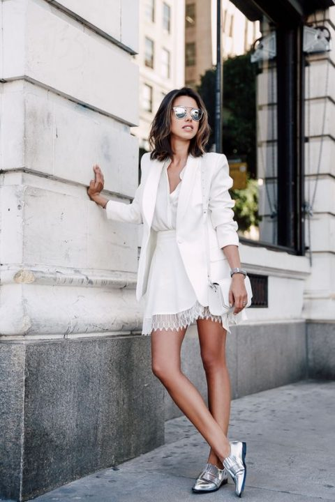 a white mini dress with a lace dge, a white blazer and metallic shoes