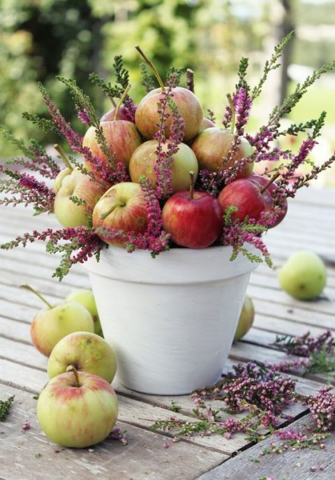 a white planter filled with apples and wildflowers for a late summer or fall wedding