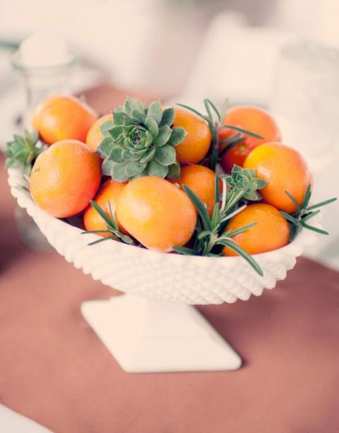a white porcelain bowl with tangerines and succulents for a tropical wedding
