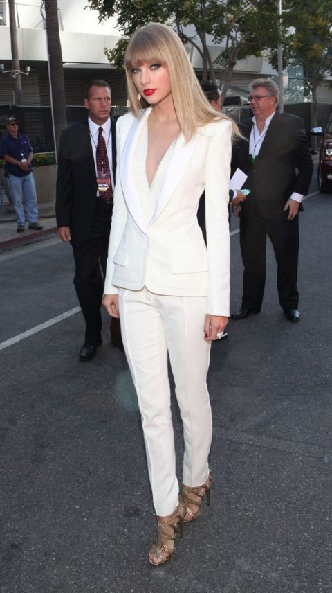 a white suit with a plunging neckline and metallic heels