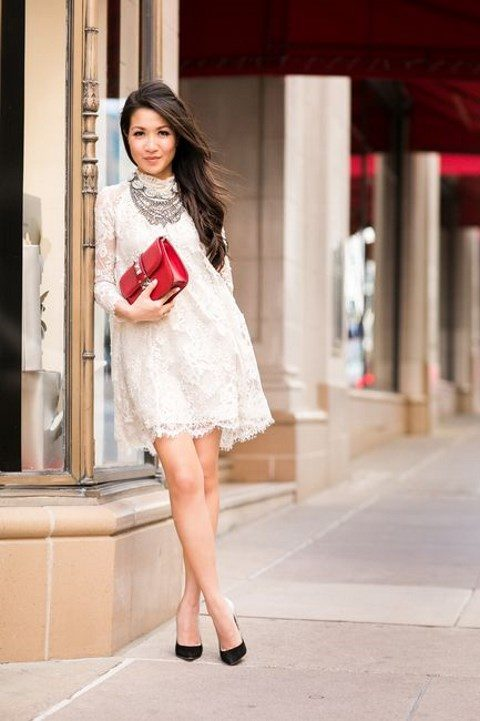 a white turtleneck lace mini dress with long sleeves, statement necklaces, black heels and a red clutch