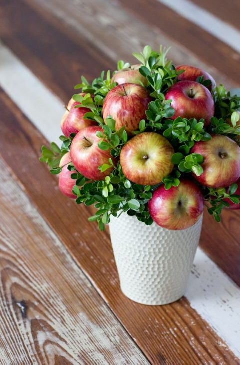 a white vase with boxwood and apples for a fall wedidng