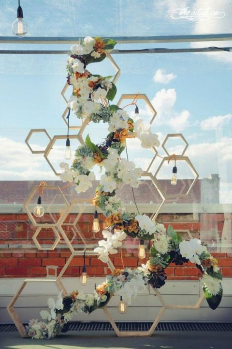 a wood wedding hexagon backdrop with bulbs and lush florals and succulents