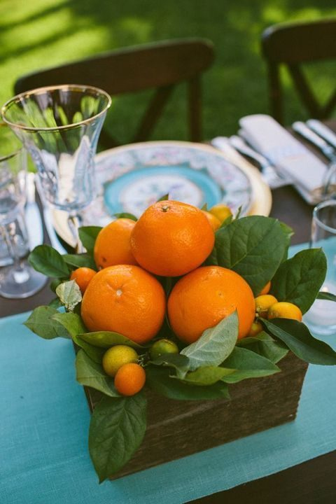 a wooden box with tangerines and kumquats for a summer or tropical centerpiece