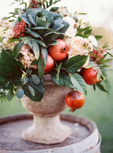 an urn with cabbage, pomegranates, greenery and blooms for a fall wedding