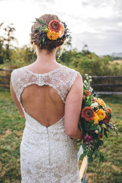 braided and twisted updo with bold fall blooms and leaves