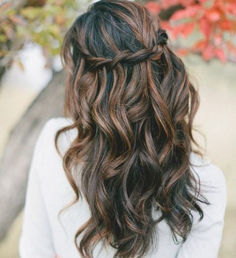 braided wavy half updo on long balayage hair