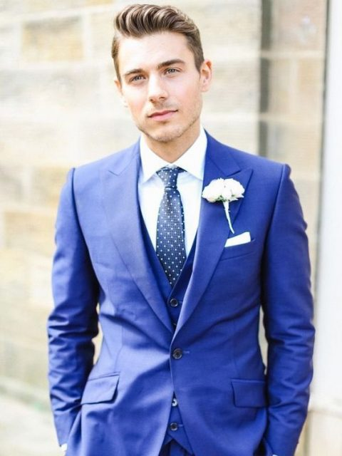 cobalt blue three piece wedidng suit with a blue polka dot tie and a white floral boutonniere