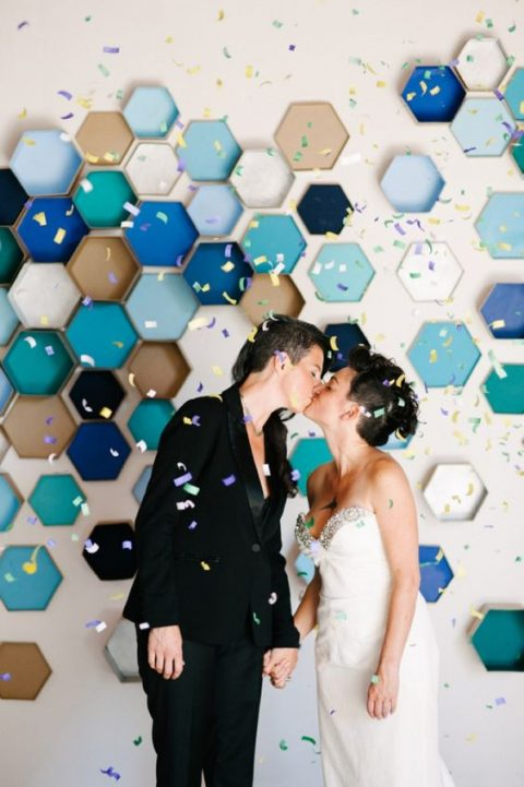 colorful hexagon backdrop was DIYed by the brides