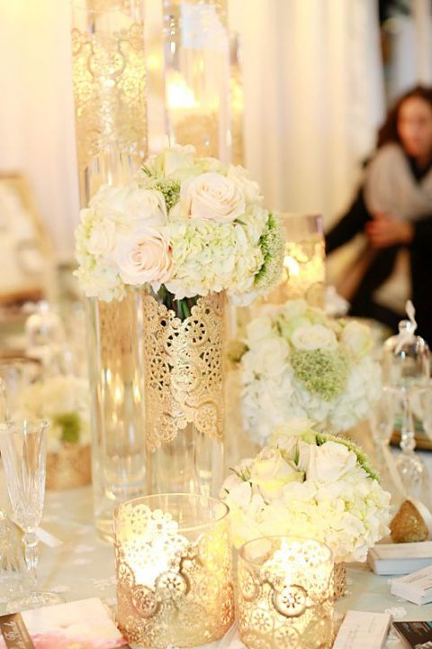glass candle holders and vases covered with gold doilies look refined