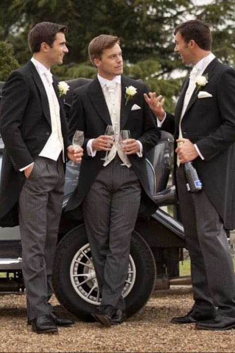 groomsmen in morning suits with striped black pants, black jackets, white vests and ties