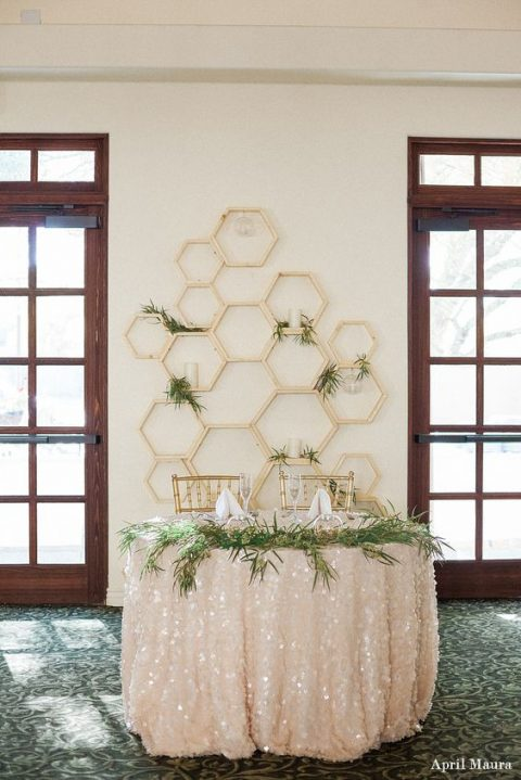 hexagon wall with greenery and candles for a sweetheart table backdrop