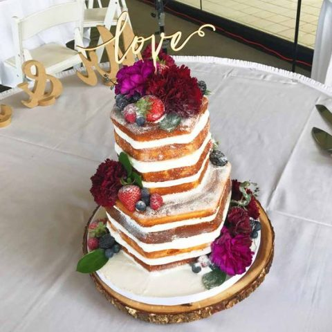 naked honeycomb shaped wedding cake with fresh berries and blooms