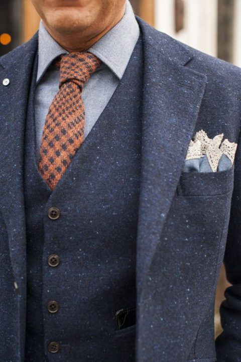 navy printed tweed suit with a chambray shirt and an orange tie