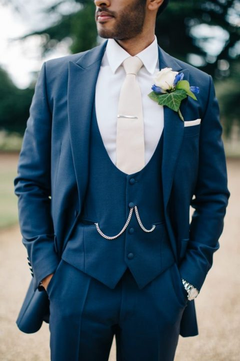 navy three piece wedding suit with a round cut vest, a white shirt and a cream tie