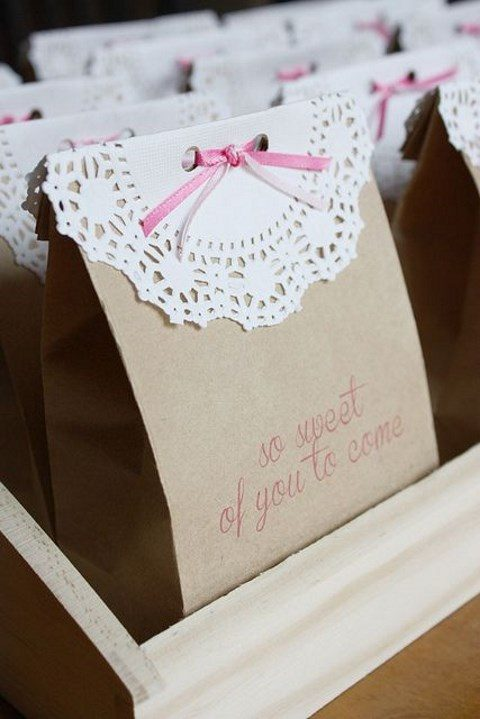 paper bags with paper doilies and pink ribbon for wedding favors