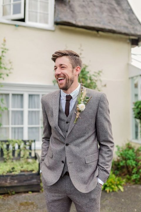 three piece grey tweed wedding suit with a brown tie and a feather boutonniere