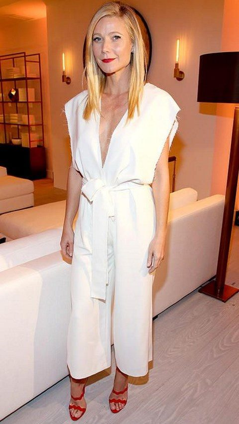 white culotte jumpsuit with a deep V-neckline and red heels