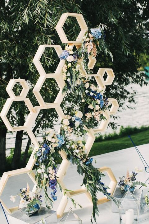 wood honeycomb wedding backdrop with greenery and blue flowers