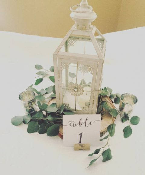 a Morocco-style candle lantern with a table number and greenery