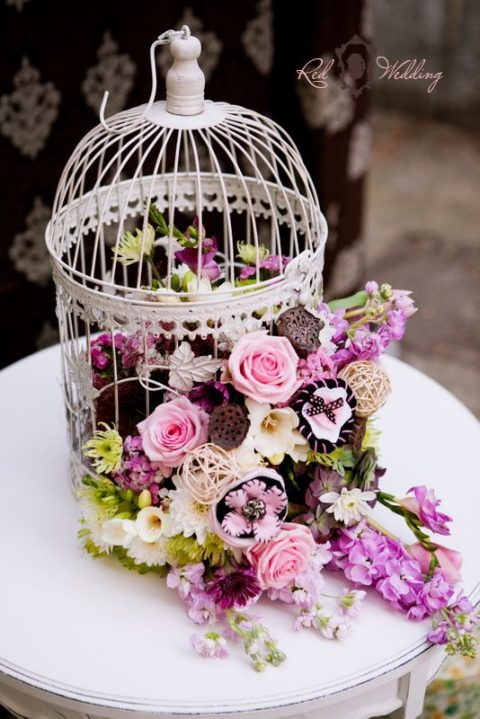 a bird cage filled with pink and other bold blooms