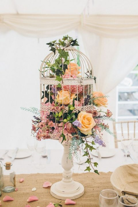 a bird cage on a wooden stand filled with flowers and greenery