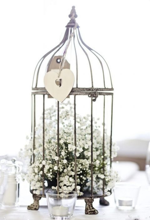 a bird cage on legs with a heart topper and baby's breath inside