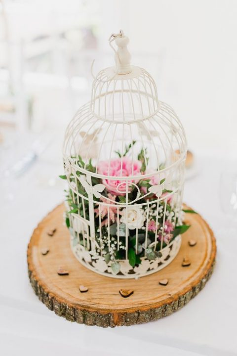 a bird cage ona wood slice with pink and white blooms and foliage