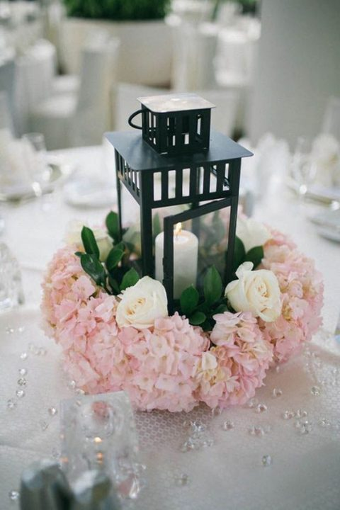 a black candle lantern surrounded with white and pink blooms