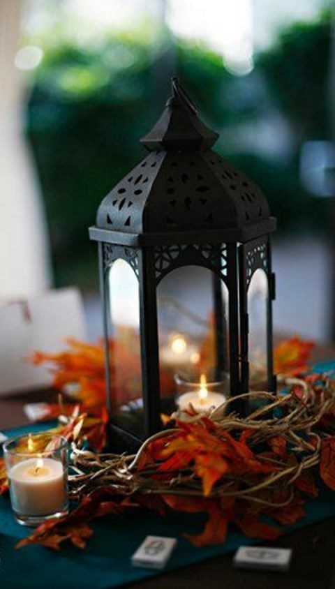 a black candle lantern with fall leaves and candles around