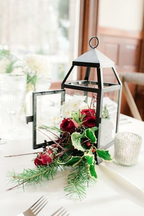a black lantern with red roses, greenery and evergreens