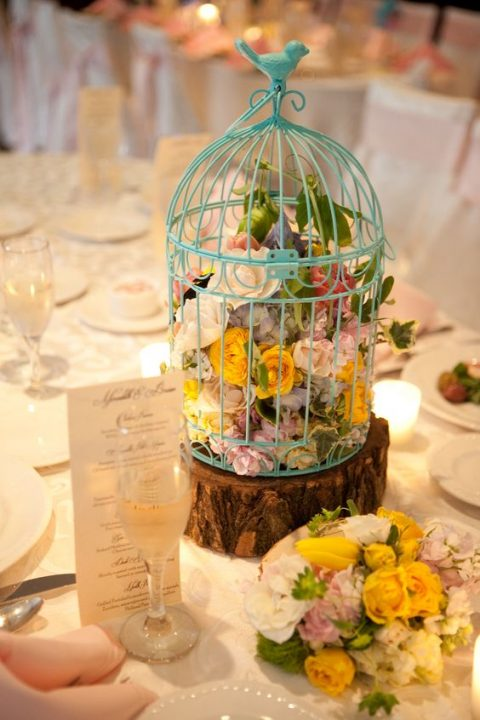 a blue bird cage on a wooden slice filled with various blooms