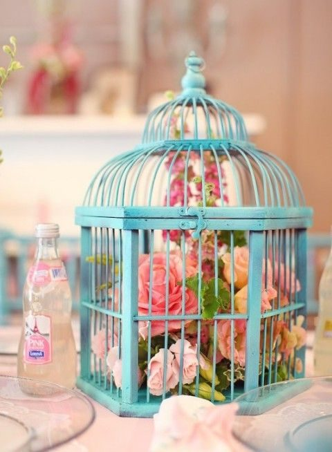 a blue bird cage with a bold floral arrangement