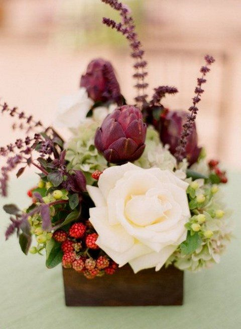 a box with a white rose, berries, herbs and artichokes
