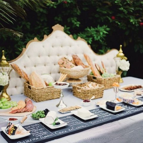 a bread-and-cheese station with a chalkboard menu, bread baskets, and a vintage headboard backdrop