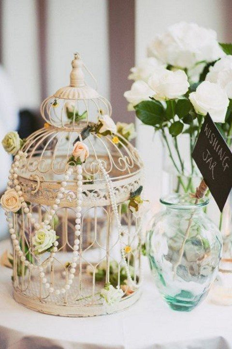 a cage decorated with peachy blooms and pearl strands