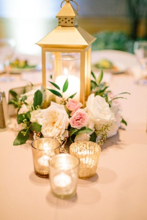a candle lantern centerpiece with blush and creamy flowers