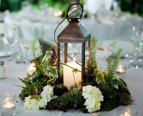 a candle lantern with moss, white blooms and foliage